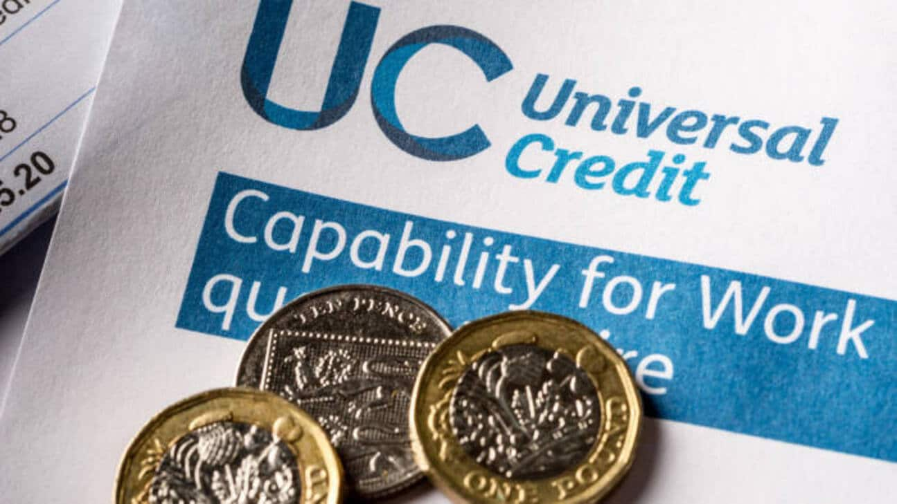 Universal Credit form with of a pile of unpaid utility-bills