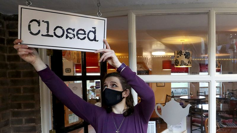 Woman with mask closing shop with closed sign